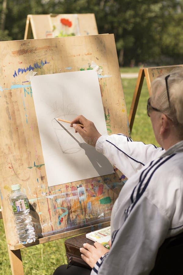 De rijpe grijs-haired vrouw trekt bloemenschets royalty-vrije stock afbeelding