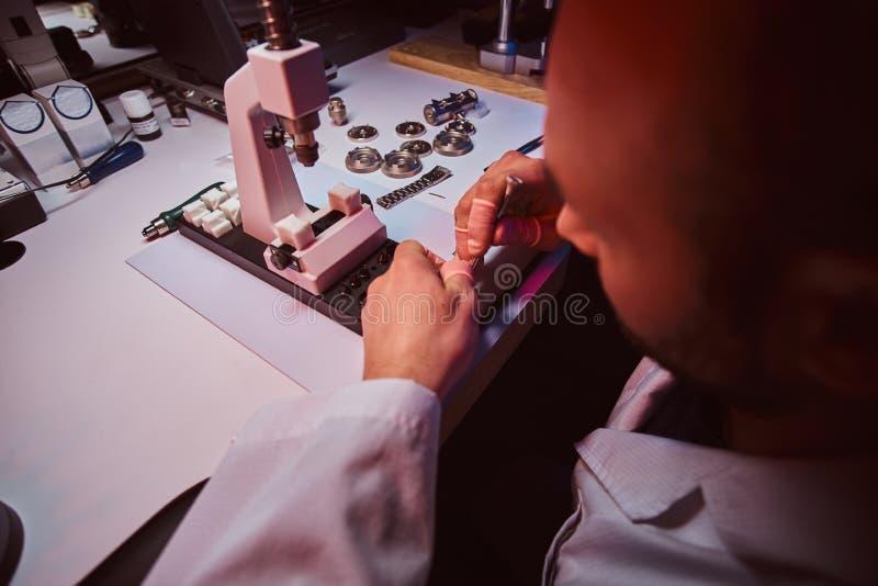 De rijpe horlogemaker werkt bij zijn eigen studio royalty-vrije stock foto's
