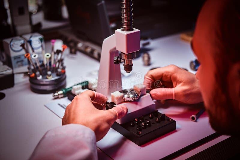 De rijpe horlogemaker werkt bij zijn eigen studio stock afbeeldingen