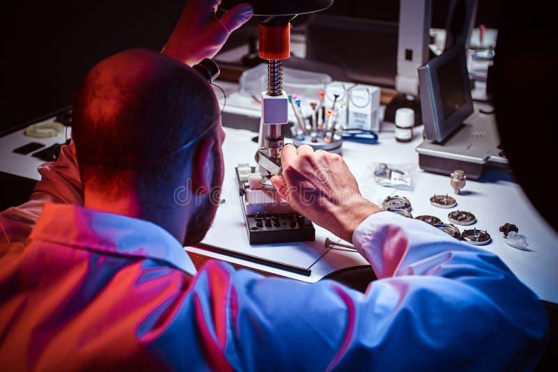De rijpe horlogemaker werkt bij zijn eigen studio royalty-vrije stock fotografie