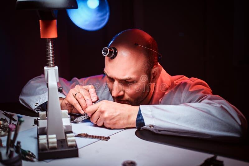 De rijpe horlogemaker werkt bij zijn eigen studio royalty-vrije stock foto