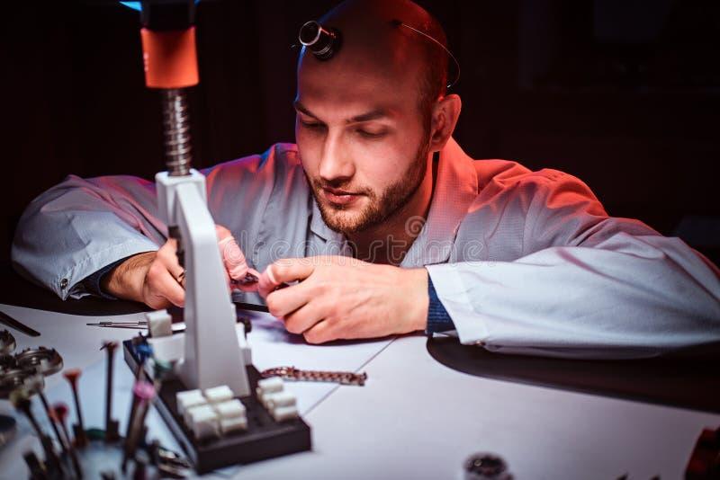 De rijpe horlogemaker werkt bij zijn eigen studio stock foto's