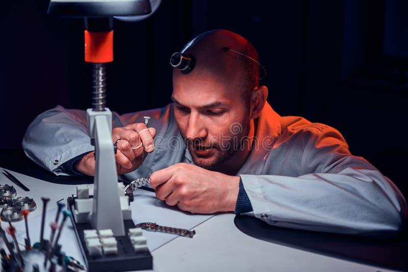 De rijpe horlogemaker werkt bij zijn eigen studio stock afbeelding