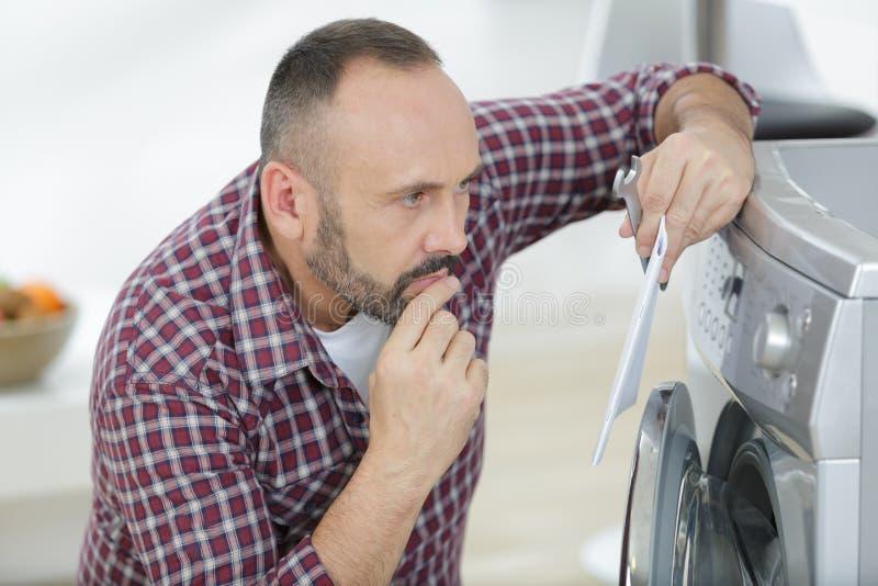De rijpe instructies van de mensenlezing voor het installeren van wasmachine stock fotografie