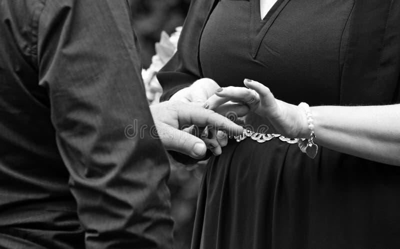 De rijpe jonggehuwden koppelen het ruilen van ringen bij huwelijksceremonie stock foto