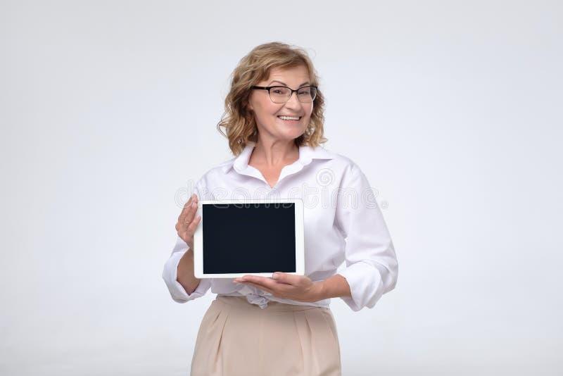 De rijpe Kaukasische vrouw toont het scherm van tabletcomputer het glimlachen royalty-vrije stock afbeelding