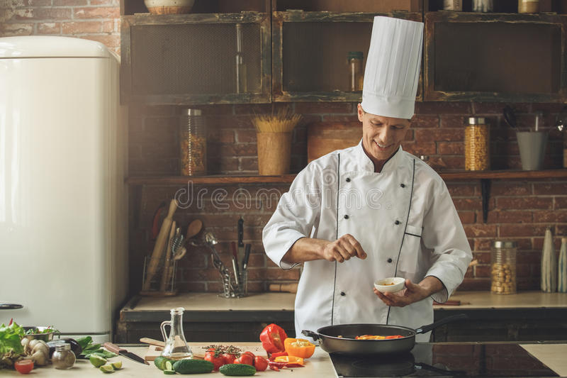 De rijpe kokende maaltijd van de mensen professionele chef-kok binnen royalty-vrije stock afbeeldingen