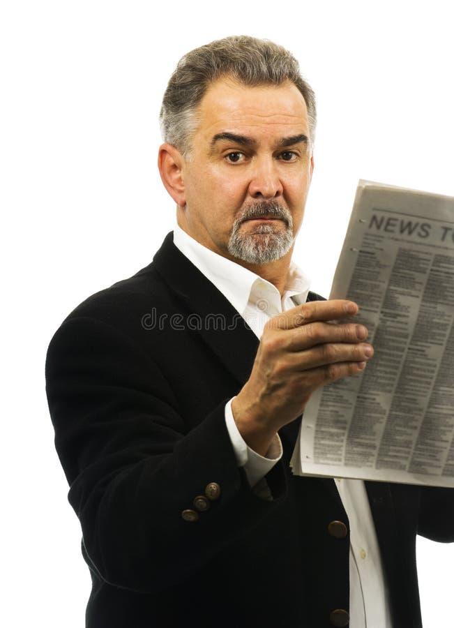 De rijpe mens houdt een krant, kijkend ernstig. royalty-vrije stock afbeeldingen