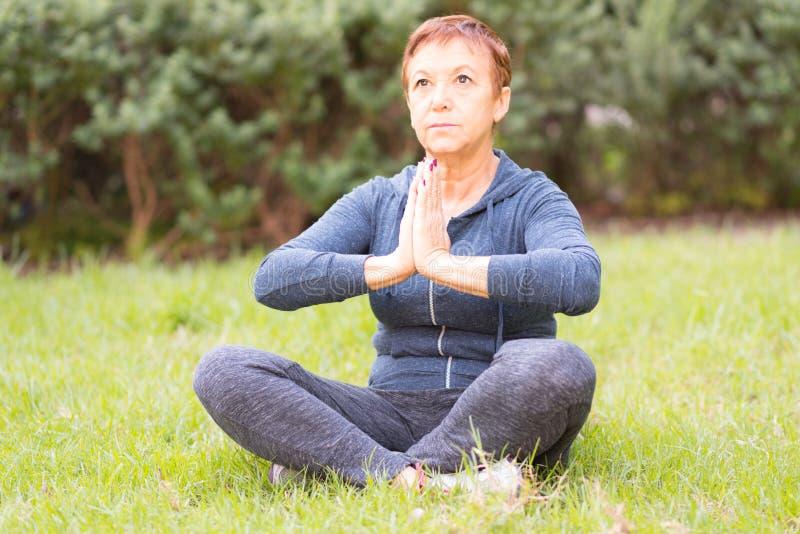 De rijpe mooie actieve gelukkige vrouw in de ochtend in het park, ontspant na sportenoefeningen De middendame in de yoga stelt stock afbeeldingen
