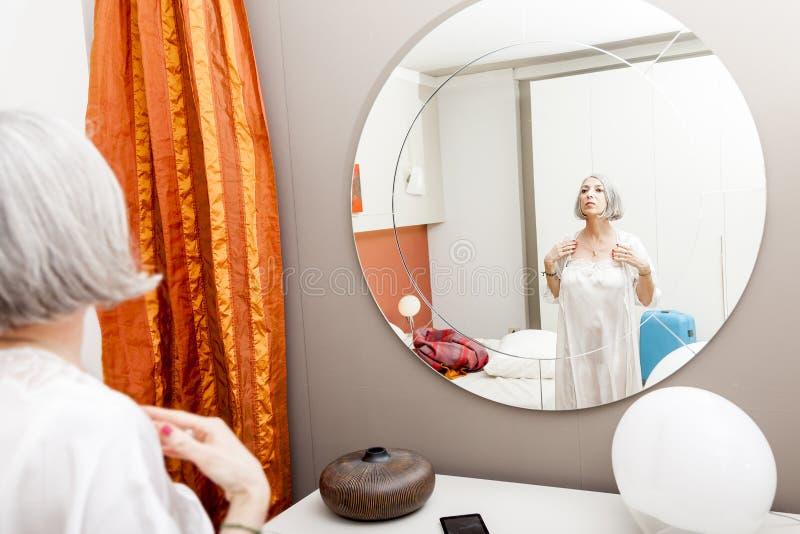 De rijpe mooie vrouw is weerspiegeld alvorens naar slaap te gaan stock fotografie