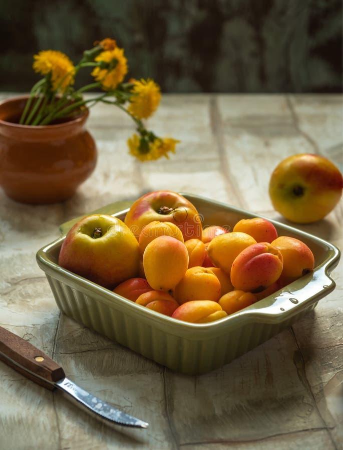 De rijpe nectarines en de abrikozen in een ceramische vierkante plaat van olijf kleuren en een klein boeket van moeder-en-stiefmo stock afbeelding
