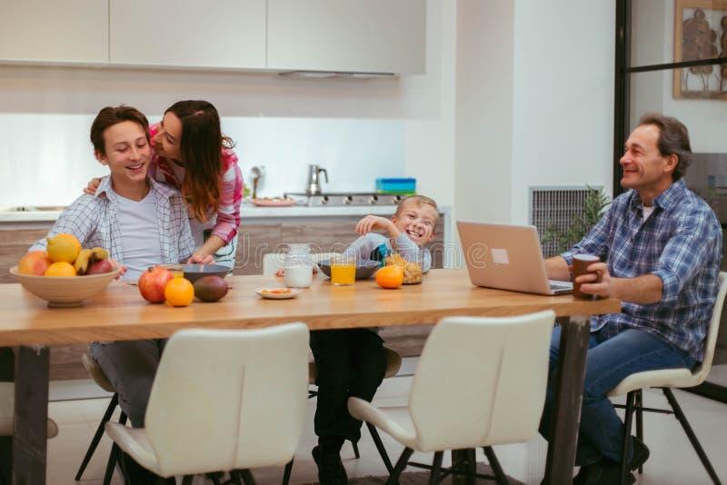 De rijpe ouders en hun kinderen hebben een eigengemaakt ontbijt samen, zijn zij zeer hongerig etend het voedsel en het voelen stock fotografie