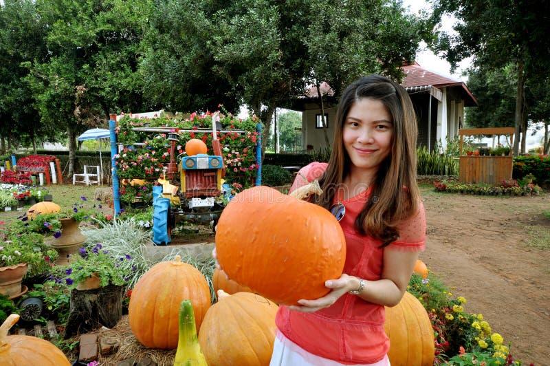 De rijpe pompoen ligt met meisje in een landbouwbedrijfgebied stock foto's
