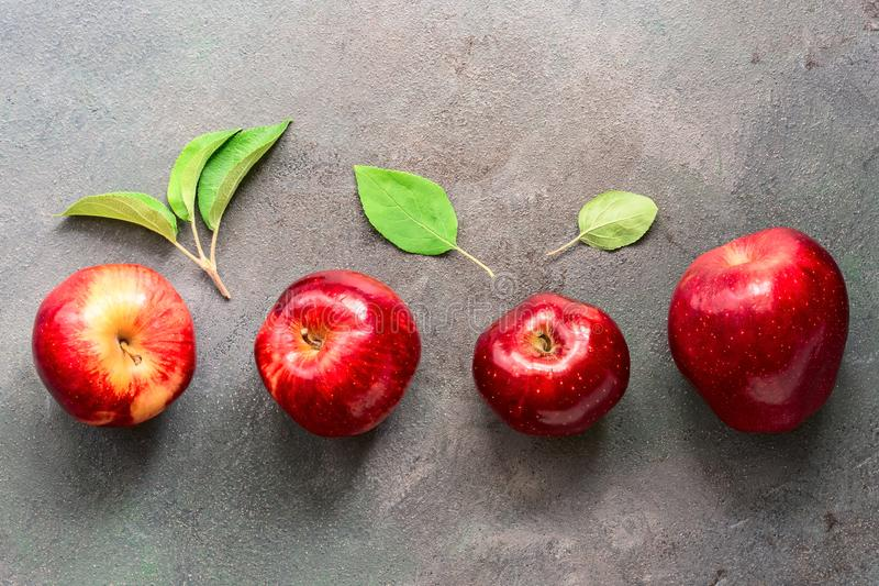 De rijpe rode appelen en de groene bladeren worden geschikt op een rij op een donkere rustieke achtergrond Vlak leg, kopieer ruim stock foto