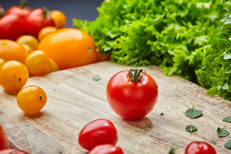 De rijpe rode en gele tomaten sluiten omhoog met groen blad en dalingen van water stock foto's