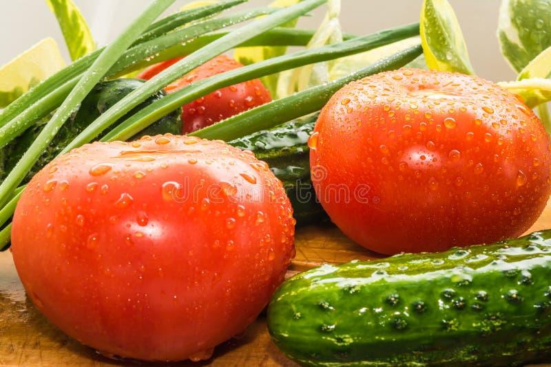 De rijpe rode tomaten, groene komkommers, groene uiveren zijn behandeld met grote dalingen van water stock foto