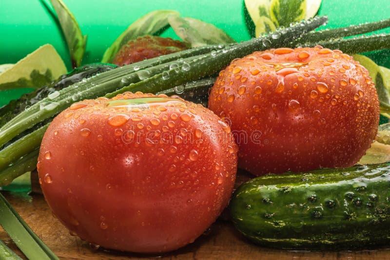 De rijpe rode tomaten, groene komkommers, groene uiveren zijn behandeld met grote dalingen van water stock afbeeldingen