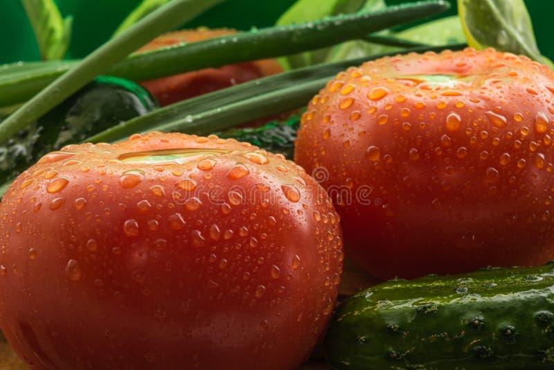 De rijpe rode tomaten, groene komkommers, groene uiveren zijn behandeld met grote dalingen van water, samenstelling op houten royalty-vrije stock afbeeldingen