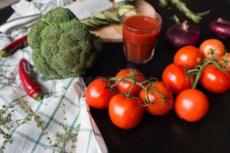 De rijpe rode tomaten liggen op een zwarte modieuze lijst op de achtergrond zien wij een glas tomatesap, rode uien stock afbeelding