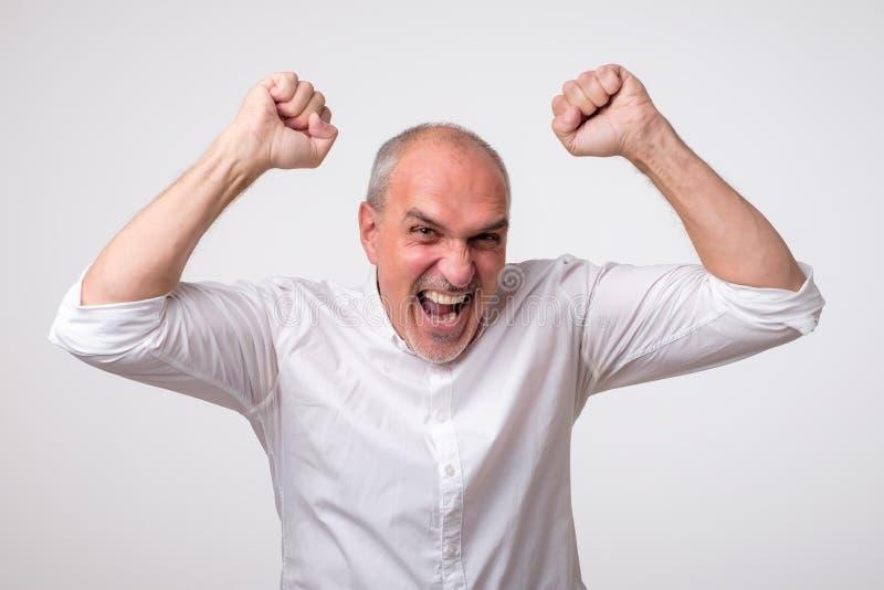De rijpe Spaanse mens is gelukkig met zijn winst Hij houdt wauw zijn vuisten en schreeuw stock foto's