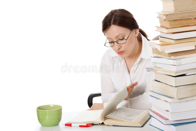 De rijpe studentenvrouw leert bij het bureau royalty-vrije stock afbeelding