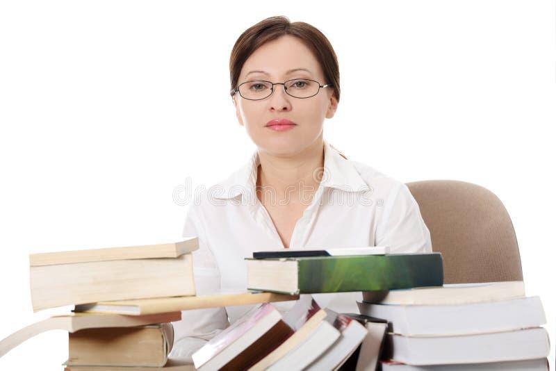 De rijpe studentenvrouw leert bij het bureau stock foto's