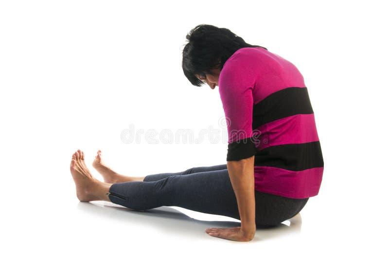 De rijpe vrouw in Dandasana-yoga stelt royalty-vrije stock foto