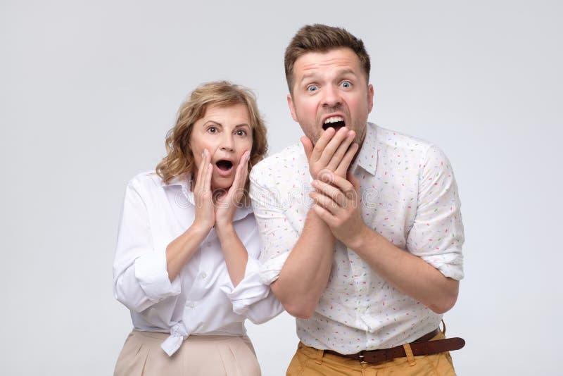 De rijpe vrouw en de man horen stuitend nieuws stock afbeelding