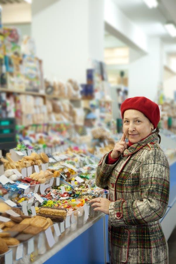 De rijpe vrouw kiest snoepjes stock afbeelding