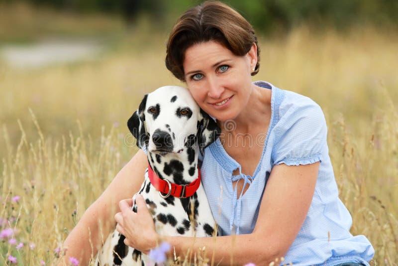 De rijpe vrouw knuffelt een Dalmatische hond in een weide openlucht royalty-vrije stock afbeelding