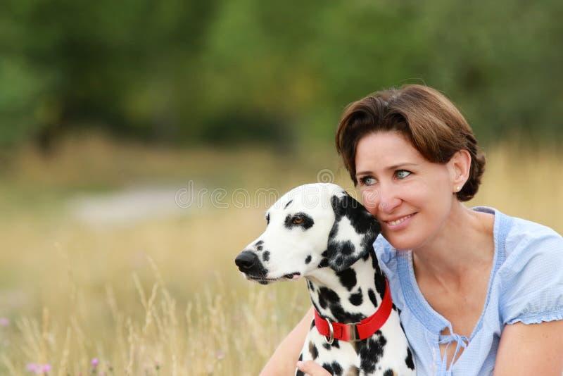 De rijpe vrouw knuffelt een Dalmatische hond in een weide openlucht royalty-vrije stock foto