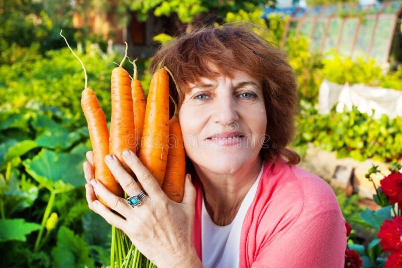 De rijpe vrouw kweekt oogst in de tuin stock foto
