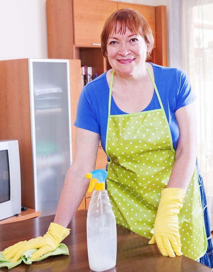 De rijpe vrouw maakt het huis schoon royalty-vrije stock afbeeldingen