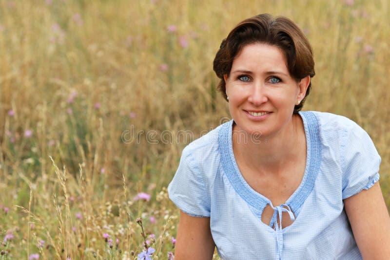 De rijpe vrouw zit op een bloemgebied in de zomer stock afbeeldingen