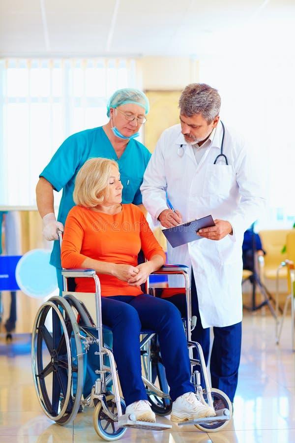 De rijpe vrouwelijke patiënt op rolstoel luistert aan het medicijn van het artsenvoorschrift stock afbeelding