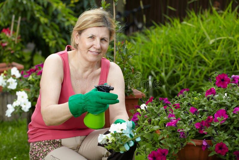 De rijpe vrouwenwerken in haar tuin stock fotografie