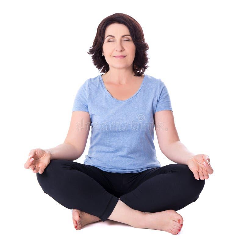 De rijpe vrouwenzitting in yoga stelt geïsoleerd op wit royalty-vrije stock afbeeldingen