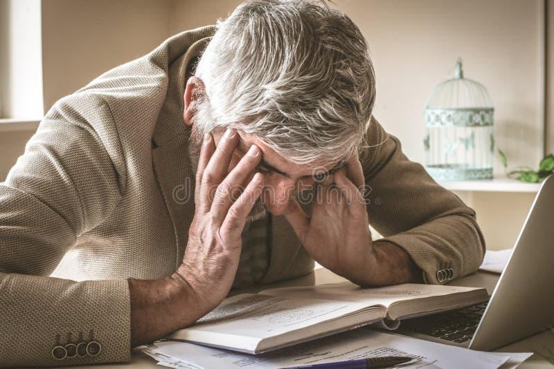 De rijpe zakenman in zijn bureau heeft hoofdpijn royalty-vrije stock afbeelding