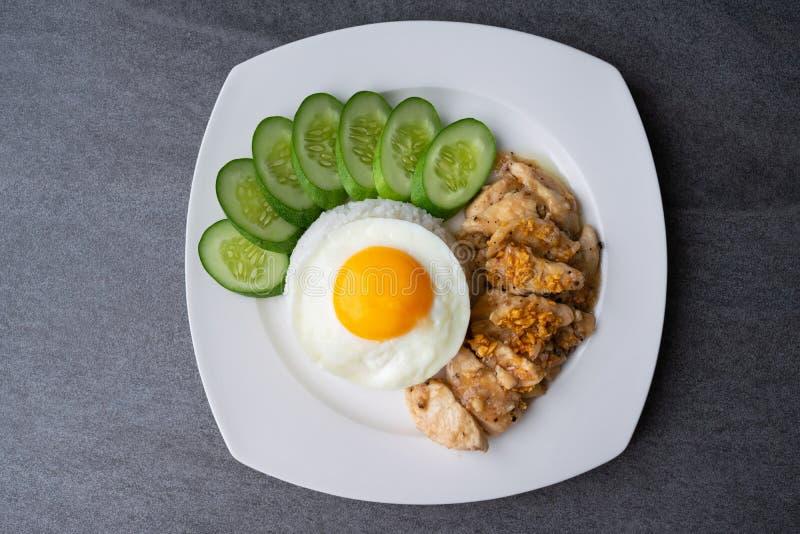 De rijst, Gebraden ei, braadde kip met knoflook en zwarte peper in witte schotel op de concrete lijst stock foto's