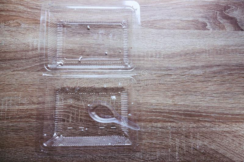 De rijst van het voedselschroot in transparant plastic voedselvakje en lepel op houten lijst stock afbeeldingen