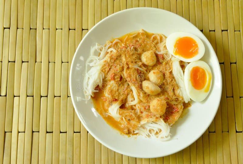 De rijstnoedels met het bovenste laagje van de vissenkerrie kookten romige eierdooier stock foto
