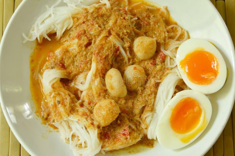 De rijstnoedels met het bovenste laagje van de vissenkerrie kookten romige eierdooier royalty-vrije stock afbeelding