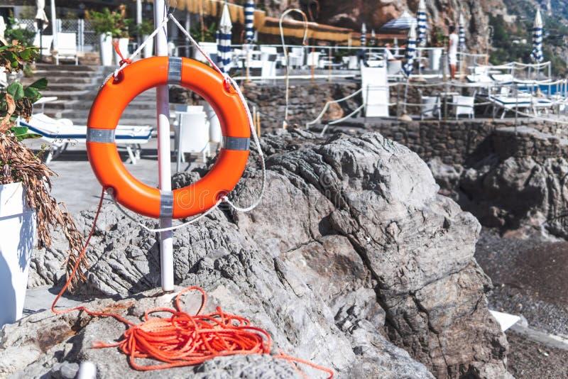 De ring van het reddingsboeileven op het steenstrand Italië stock foto's