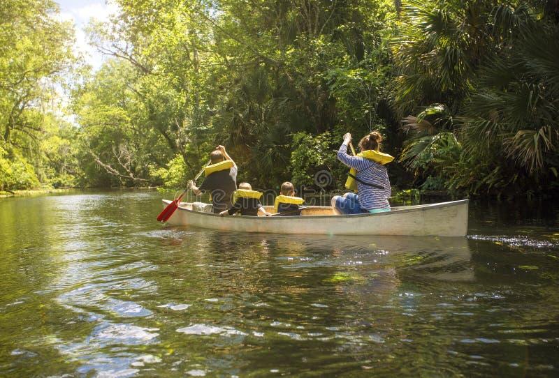 De rit van de familiekano onderaan een mooie tropische rivier royalty-vrije stock afbeeldingen