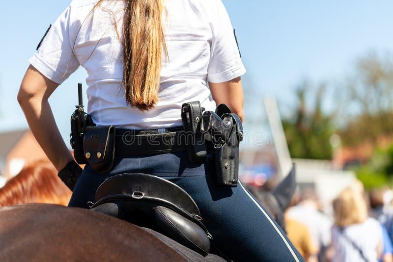 De ritten van de politieamazone op een politiepaard stock foto's