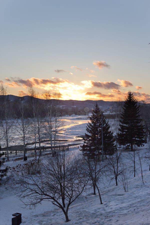 De rivier in de winter bij zonsondergang in Rusland stock foto