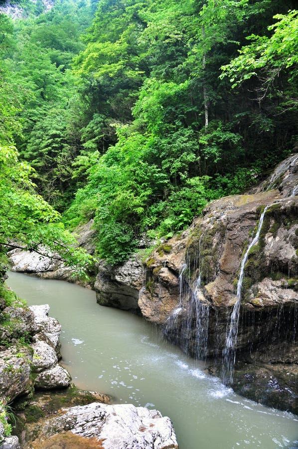 De rivier en de watervallen van de landschapsberg met grote rotsen op de kust stock foto's