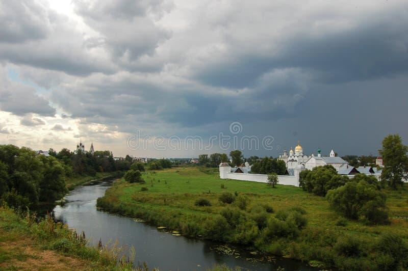 De rivier omringt het oude klooster Daar ` s een onweer komst Suzdal, Rusland stock foto's