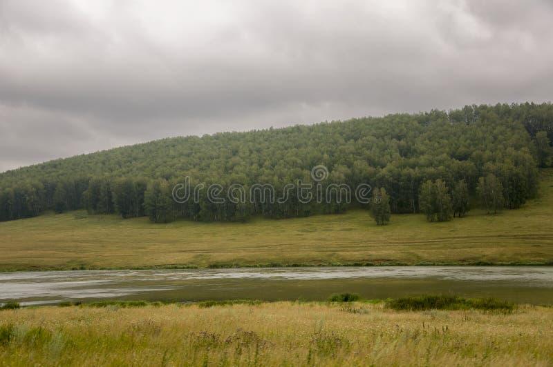 De rivier stroomt langzaam De grijze wolken in de vroege de herfsthemel over groene gebieden, bomen, bossen en reusachtige bergen royalty-vrije stock foto