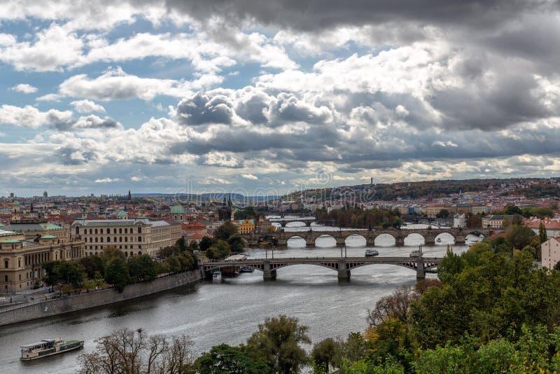 De rivier van Praag met bruggen en bewolkte hemel stock foto's